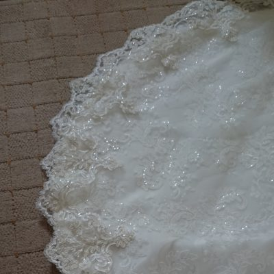 Lace edging on the detachable train of a beaded lace and tulle wedding gown