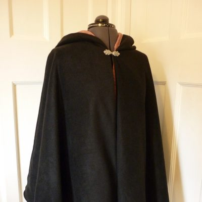 black fleece cape with a gold lining